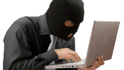 person wearing a ski mask and holding a laptop